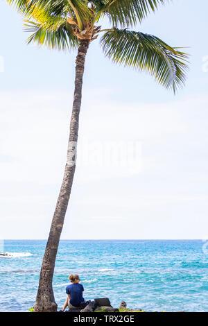 Une femme assise seule, contemplant, sous un palmier, Hilo, Hawaii. Banque D'Images