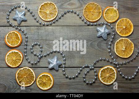 Composition de Noël avec silver bead chain, brocade stars et les tranches d'orange sur fond de bois Banque D'Images
