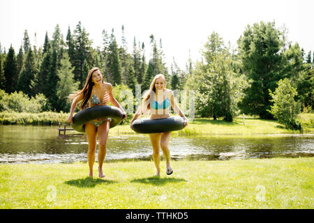 Happy female friends avec anneaux gonflables walking on grassy field Banque D'Images