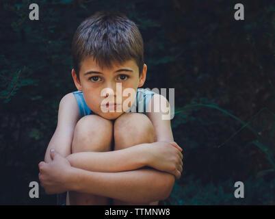 Portrait of boy hugging déprimé les genoux à yard Banque D'Images