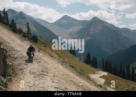 Biker riding sur route de montagne contre le ciel Banque D'Images