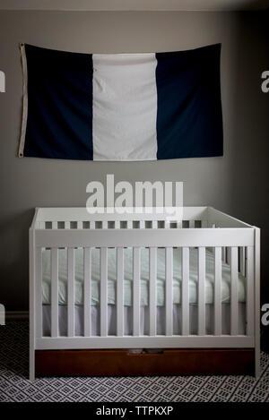Lit-bébé contre drapeau rayé pendaison sur le mur dans la chambre à la maison Banque D'Images