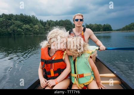 Sœur kissing girl alors que père canoë dans le lac contre les nuages orageux Banque D'Images