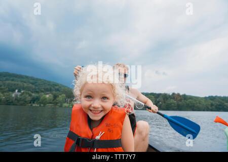 Fille heureuse avec le père en canoë kayac en arrière-plan contre les nuages orageux Banque D'Images