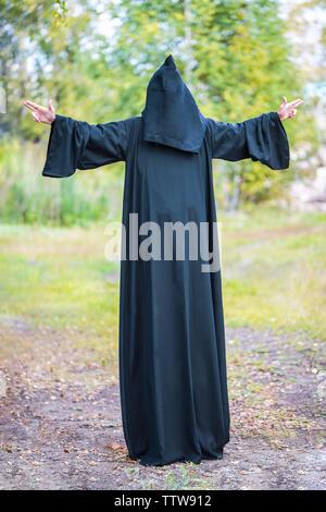 Un homme de grande taille dans un costume noir avec une capuche répandre ses mains sur les côtés, montrant les gestes. La photographie verticale Banque D'Images