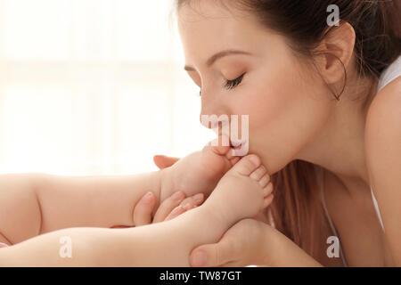 Mère embrassant les pieds de son bébé à la maison Banque D'Images