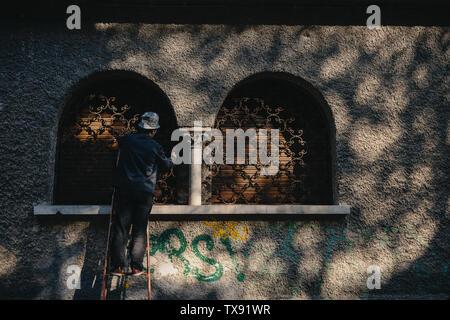 Un homme travaille sur une fenêtre à Bucarest, Roumanie. Banque D'Images