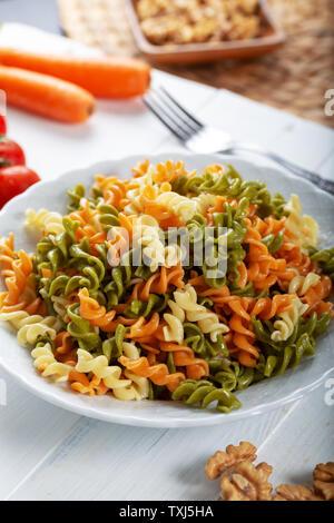 Pâtes multicolores avec légumes légumes ve sur fond de bois Banque D'Images