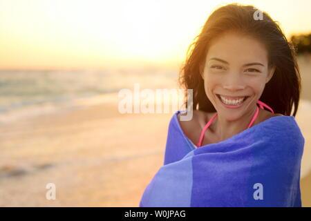 Plage de baignade avec serviette femme heureux portrait. Young pretty Young Asian Woman wrapped in towel standing in beach au coucher du soleil. Smiling happy bénéficiant des vacances voyage vacances. Hawaii. Banque D'Images