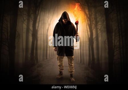 Homme Mystérieux venant d'un chemin dans la forêt avec brûler flambeau concept Banque D'Images