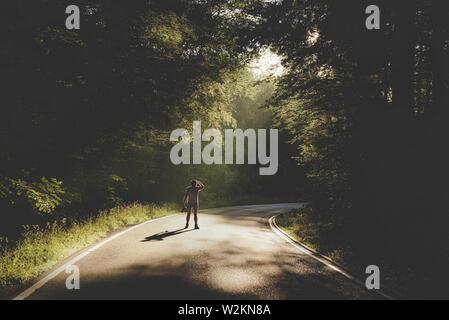Randonneur marchant sur la route dans une forêt ombragée. Matin les rayons du soleil à travers les arbres sur la route. Banque D'Images