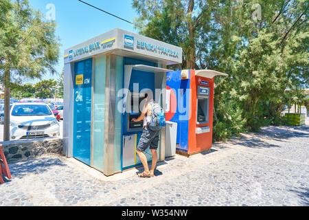 Prend de l'argent à touristiques cash machine ATM de la Banque nationale à la plage près de l'aéroport et de Fira et Oia, Santorin, Grèce au 06 juin.2019. © Peter Sc Banque D'Images