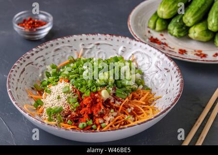 Préparation des produits pour la cuisine coréenne traditionnelle kimchi de concombre snack: mélanger les ingrédients dans une assiette, les aliments fermentés, photo horizontale Banque D'Images