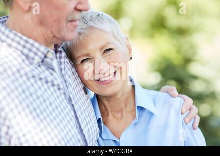 La mi-section portrait de senior couple embracing, focus sur elegant woman smiling at camera, copy space Banque D'Images