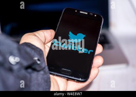 Nizhyn, Ukraine/Juillet-16-2019: jeune représentant l'homme en noir de tenir et de l'utilisation du smartphone application Twitter. Les médias sociaux et corporatifs concept. Banque D'Images