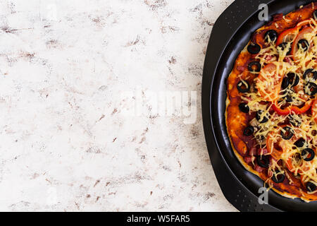 Pizza au salami, poivrons, champignons et olives sur fond blanc. Vue d'en haut Banque D'Images
