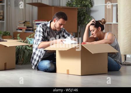 Expulsées triste couple moving home boxing biens assis sur le plancher dans la nuit Banque D'Images