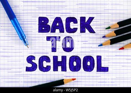 Hand drawn doodles message Retour à l'école sur du papier à carreaux avec stylo à bille bleu et des crayons. Banque D'Images