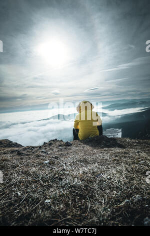 Hiker homme prendre un repos sur la montagne. L'homme s'asseoir sur le sommet pointu et profiter d'une vue spectaculaire. Paysage d'automne. Soleil du matin lumineux brillant dans s Banque D'Images