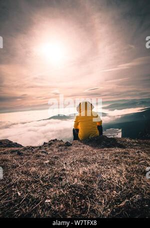 Hiker homme prendre un repos sur la montagne. L'homme s'asseoir sur le sommet pointu et profiter d'une vue spectaculaire. Banque D'Images