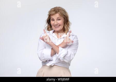 Young smiling woman pointant dans deux directions différentes. Banque D'Images