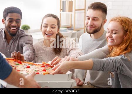 Livraison de pizza. Les amis de prendre des tranches de pizza chaude Banque D'Images