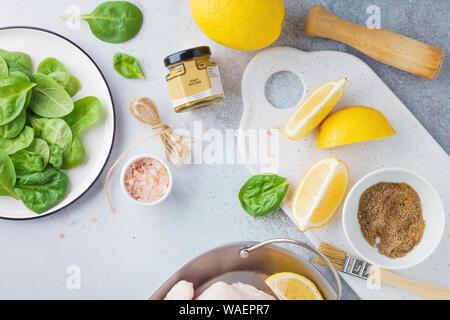Ingrédients pour un dîner de fête ou le déjeuner. La dinde crue ou de poulet, citron, épinards, d'épices et moutarde au miel. Concept de cuisine mise à plat. Banque D'Images