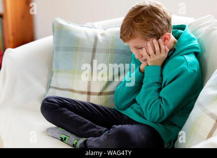Garçon à la dépression était assis sur un canapé Banque D'Images