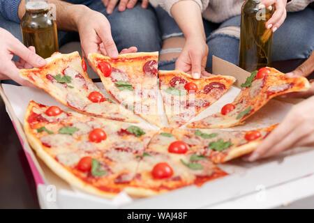 Livraison de pizza. Les amis de prendre des tranches de pizza délicieuse Banque D'Images