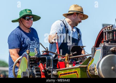 Hellingly, Sussex, UK. 25 août 2019. Deux hommes souriant pendant la conduite d'un moteur de traction à vapeur au Festival des transports Hellingly show. Banque D'Images