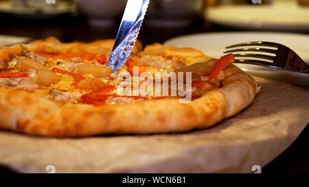 Couper et servir avec de la viande pizza italienne, bacon, pepperoni et fromage Banque D'Images