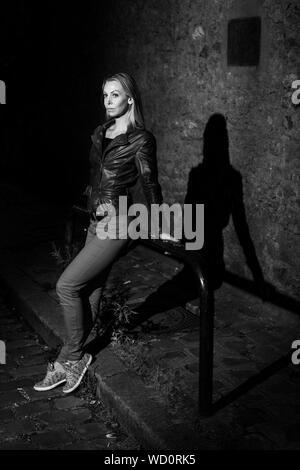Paris, France - le 2 juillet 2017: Young blonde woman standing seul la nuit sur rue en centre ville de Paris, noir et blanc Banque D'Images