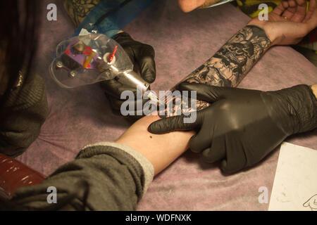 Kharkiv, Ukraine - Avril 08, 2017: détail de la main d'un maître de tatouage en gants noirs avec un tatouage machine rend un tatouage selon les sketc Banque D'Images