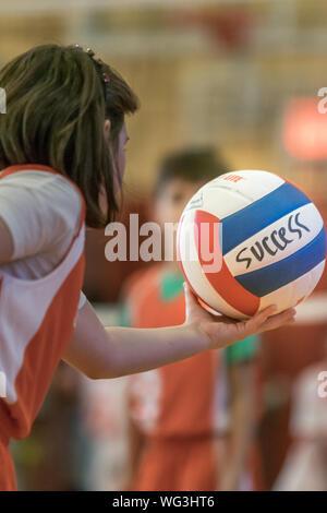 Jeune fille sur le point de servir, holding a volleyball avec succès le mot écrit dessus Banque D'Images