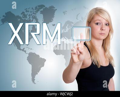 Jeune femme étendue numérique appuyez sur le bouton sur l'interface de gestion des relations en face d'elle Banque D'Images