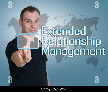 Jeune homme press digital Extended Relationship Management interface sur le bouton en face de lui Banque D'Images