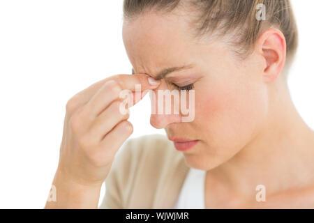 Femme avec des maux de pincer son nez sur fond blanc Banque D'Images