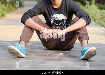 Close up Portrait of young sportsman, athlète homme dans les vêtements de sport assis sur la voie et champ près de jeux pour enfants, pour se détendre après le jogging ou la guerre Banque D'Images