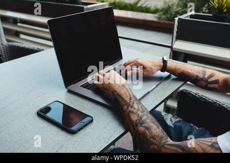 Les jeunes tattooed man working on laptop in cafe. Vue arrière de la main de l'ordinateur portable à l'aide de tatouage avec bureau en coworking 24. Beau mec taper le texte sur Banque D'Images