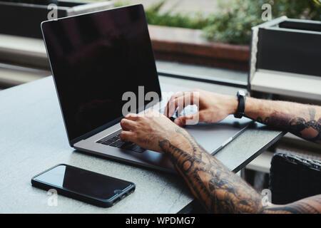 Les jeunes tattooed man working on laptop dans un café. Vue arrière de la main de hipster tattoo at occupé bureau coworking 24. Guy tapant t Banque D'Images