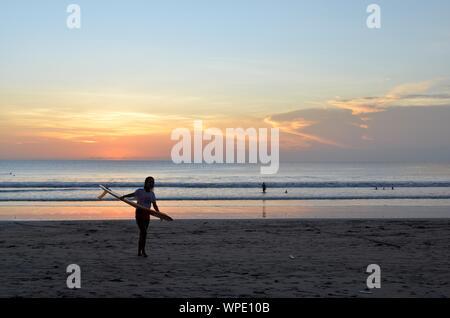 Un beau coup d'une femme portant un surf sur la rive avec un ciel bleu en arrière-plan Banque D'Images