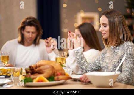 Belle famille priant sur dîner de fête à la maison Banque D'Images