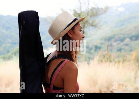 Music Concept: jeune et belle femme portant un étui rigide d'une guitare acoustique. Banque D'Images