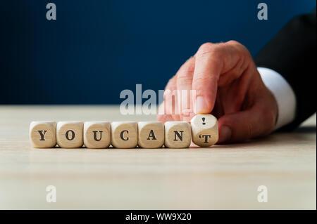 Part d'un changement d'un homme d'affaires Vous ne pouvez signer sur les cubes en bois dans une Vous pouvez! En inversant les dés. Banque D'Images