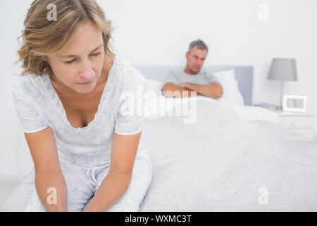 Couple assis aux extrémités opposées du lit après un combat à la maison dans la chambre Banque D'Images