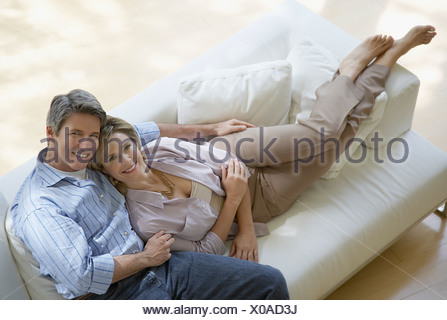 Couple dans la salle de séjour se prélasser ensemble sur canapé Banque D'Images