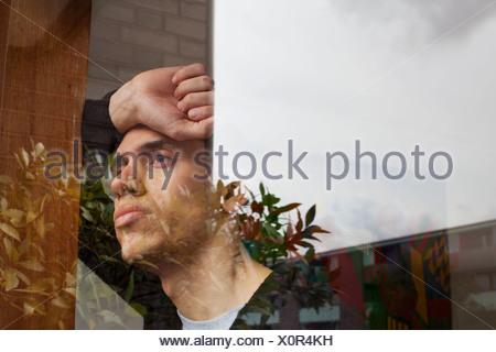 Jeune homme avec la main sur la tête, à la recherche d'une fenêtre Banque D'Images