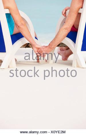 Close Up of Senior Couple Holding Hands Beach dans des chaises Banque D'Images