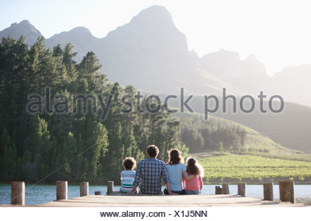 Family sitting on lake dock Banque D'Images