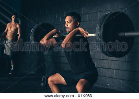 Man lifting barbell in gym Banque D'Images